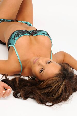 A sexy young woman laid on her back in blue lingerie