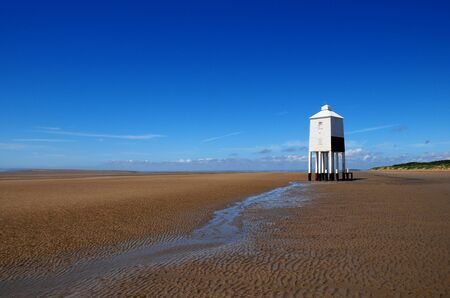 White timber lighthouse on a beach in summer Stock Photo