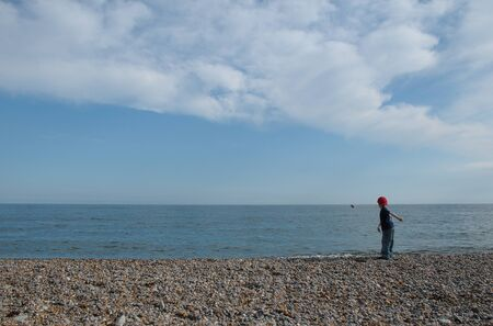 young boy throwing stones into the sea