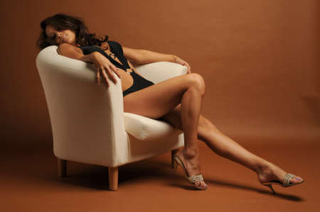 A sexy young woman in a skimpy swinsuit sat in a white chair Stock Photo