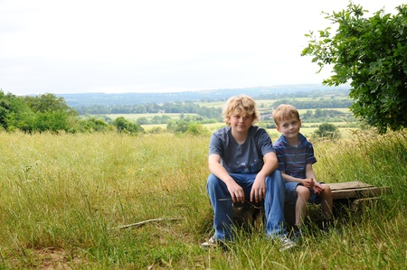 two young brothers resting on a bench in a wild meadow