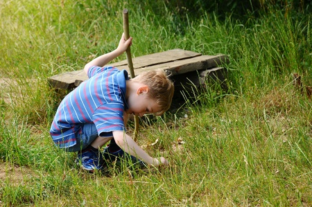 crouched: A young boy playing and exploring in a field