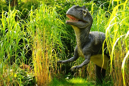 An animated model of an Allosaurus dinosaur emerging from long grass
