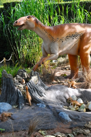 a model of an Edmontosaurus dinosaur with babys in nest site