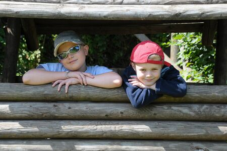 two young brothers playing in and looking out of  a den Stock Photo