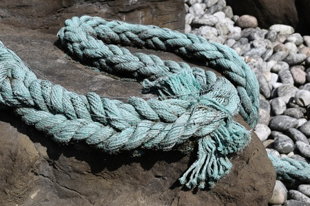 an old fraid rope coiled around and over a rock