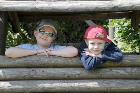 Two young brothers in caps smiling and playing in a wooden den Stock Photo