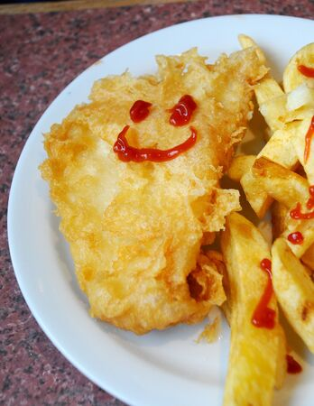 Kids meal of fish and chips with a smiley face drawn in tomato sauce