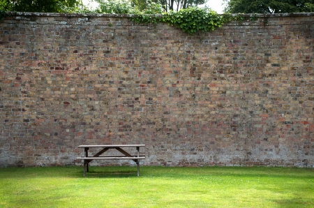 a wooden picnic table on the lawn infront of an old brick wall