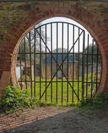 A circular hole and gate way through a wall to a country garden  Stock Photo