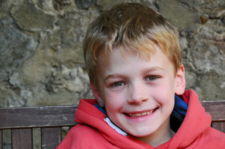 A happy young boy wearing a red hoody  photo