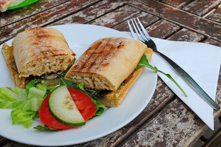 A light pub lunch of a toasted panini with dressing on a picnic table  Stock Photo