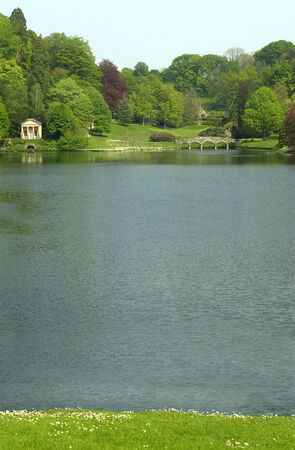 A view across Stourhead lake to th ebridge and boathoue