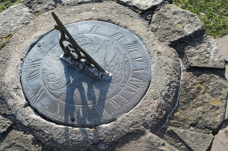 A brass sundial mounted on a stone plinth
