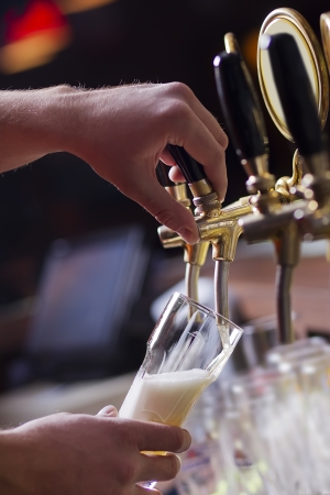 pouring beer: waiting man pouring beer into the glass Stock Photo