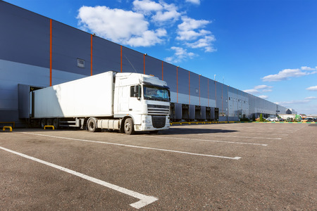warehouse building: White cargo truck at warehouse building Stock Photo