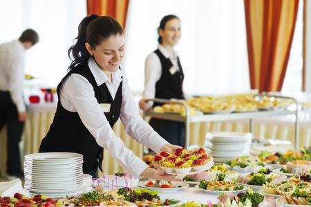 Restaurant waitress serving table with food Фото со стока
