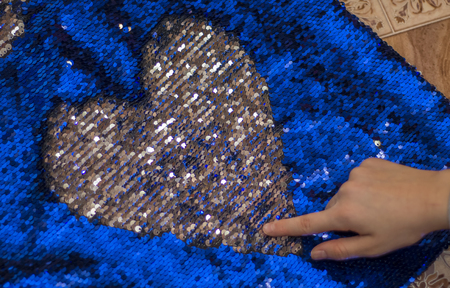 girl draws heart on blue fabric with double-sided sequins