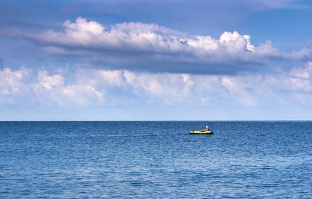 fisherman in a boat rowing oars