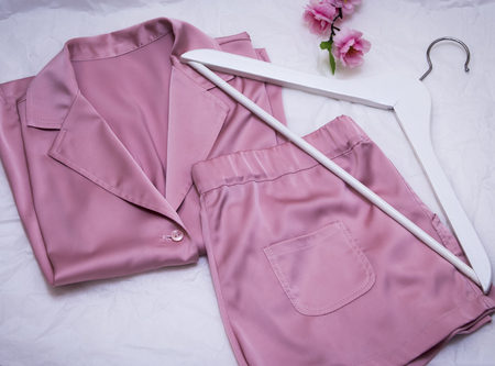women's silk pink pajamas with hanger and flowers on white background