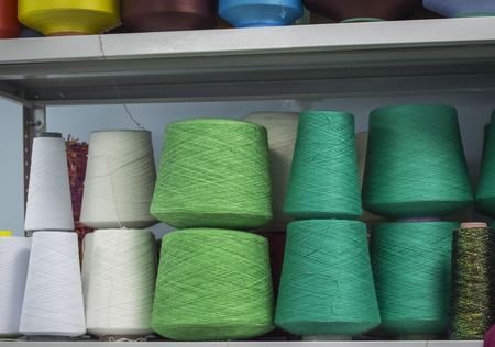 cotton and wool yarn on the spools on the shelf in the production.