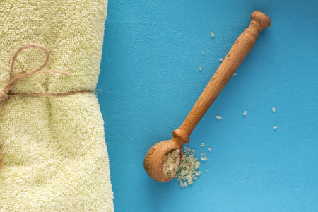 Green salt for Spa in a spoon, with a towel, top view