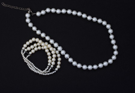women's jewelry with pearls on black background.