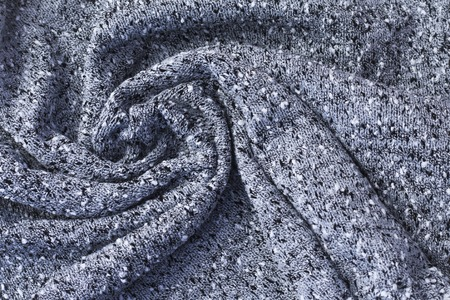 textured background of gray fabric twisted into a spiral.