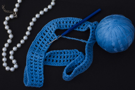 skein of blue thread with crochet and knitting on black background with pearl beads for women. Archivio Fotografico