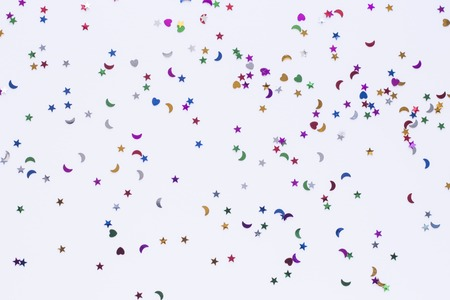 colored sequins of different shapes on white background.