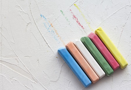 colored crayons lined in a row on a white textured background with a copy of the space. Фото со стока