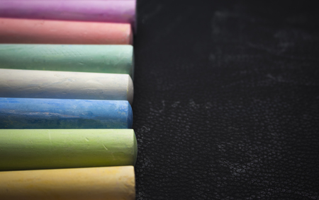 colored children's crayons on a black background lined with a copy of the space.