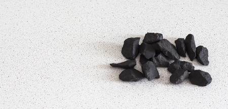 shungite stones on white background with copy space.