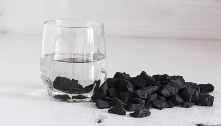Russian shungite stones on a white background used in alternative medicine for water purification and recharge due to high carbon content and metaphysical properties.