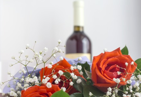 red variegated roses on a white background with a bottle of wine in the background.