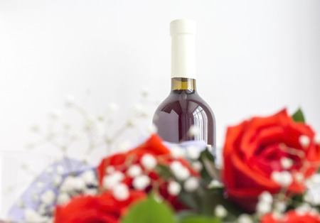 a bottle of wine with blurred red roses in the foreground. Imagens
