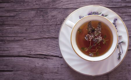 herbal tea with a bunch of fresh wild thyme on an old wooden background.the view from the top. Stok Fotoğraf - 129255229