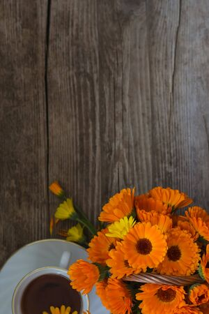 a Cup of tea with a bouquet of calendula on a wooden background with a copy of space.