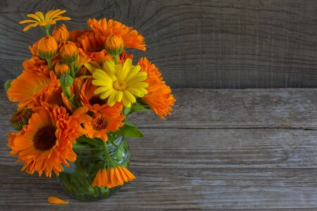 bouquet of calendula on an old wooden background with a copy of space.