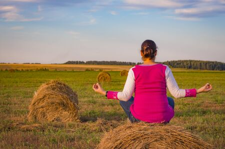 a woman meditates in a field on a haystack at sunset.
