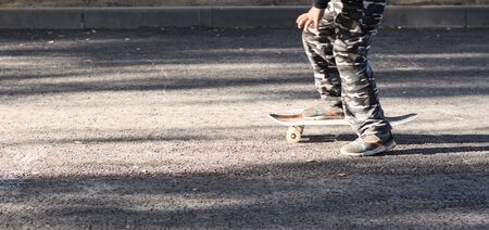 a child skateboards on the asphalt of the city in Sunny weather with a copy of the space