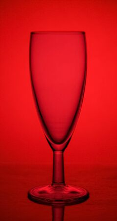 empty glass champagne glass on the lumen on a red background