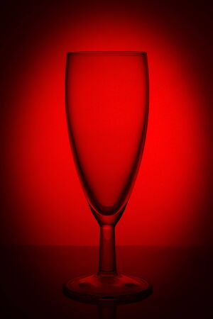 empty glass champagne glass on the lumen on a red background with a vignette