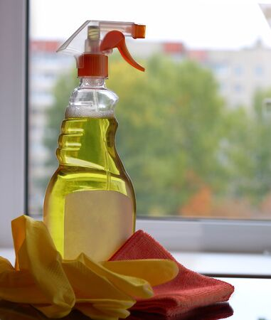 Cleaning concept.yellow spray cleaner with gloves and cloth on dirty window background Stok Fotoğraf