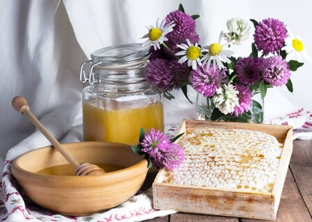 still life with fresh honey and flowers on a woven towel background.