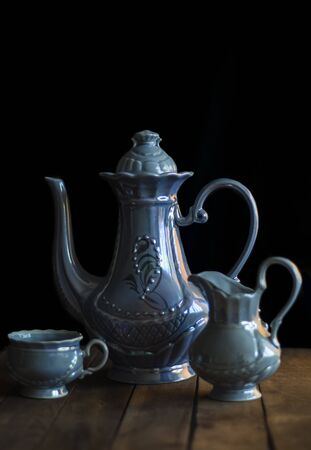 still life with a blue coffee set consisting of a teapot with a milkman and a Cup on a black background .
