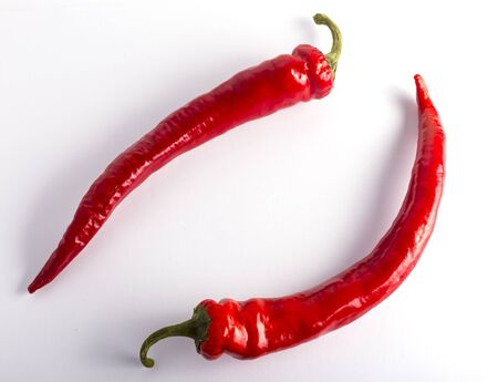 two red chili peppers on a white background.