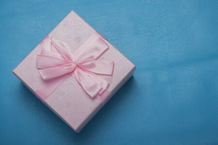 beautiful pink gift box with bow on blue skin background.