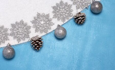silver snowflakes on the background of white fluffy winter Jersey with Christmas balls and cones.