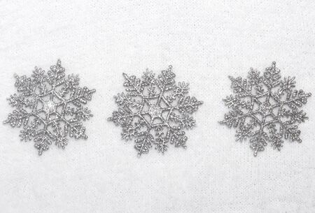 three silver snowflakes on a background of white fluffy winter Jersey